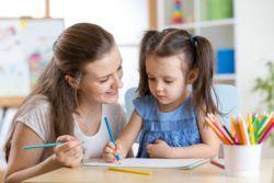 Niñera ayudando a niña con los deberes