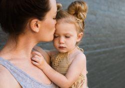 madre besando a hija en brazos