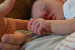 padre y bebé agarrado a su mano