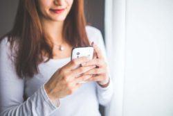 mujer mirando teléfono móvil para buscar niñera a domicilio