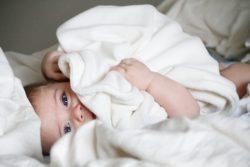 muerte súbita del bebé, niño tapándose en cama